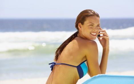 Woman in bikini outdoors talking on cell phone